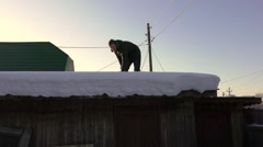 Young guy knocks the snow off the roof Stock Footage
