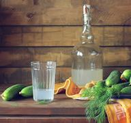 Still life with moonshine and fresh cucumbers. - stock photo