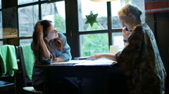 Blonde chatting on cellphone in the cafe and her friend looking bored - stock footage