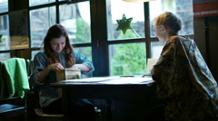 Brunette showing new scarf to her friend in the restaurant Stock Footage