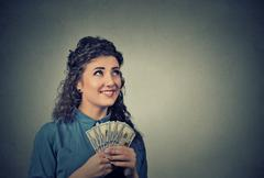 happy successful business woman holding money dollar bills in hand looking up - stock photo