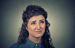 confused skeptical young woman thinking looking up - stock photo