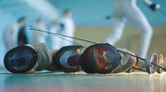 Fencing mask and foil and fencers on background Stock Footage