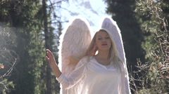 Blonde girl in a white dress with angel wings backlit sunlight. Stock Footage