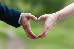 Male and female hand connected in form of heart - stock photo