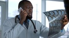 Male doctor viewing mri scan and speaking cell phone Stock Footage