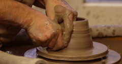 Man shapes pottery as it turns on wheel. Slow motion. Stock Footage