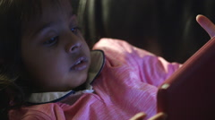 Cute little girl in the dark looking at her tablet pc Arkistovideo