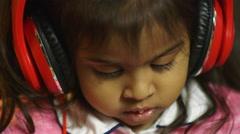 Closeup of little girl wearing headphones Stock Footage