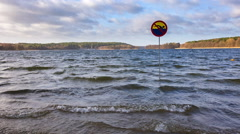 Lake shore with no swimming sign Stock Footage