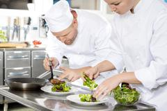Two chefs prepares steak dish at gourmet restaurant Stock Photos