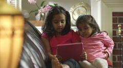 Cute Indian children sitting on a couch watching a tablet pc Stock Footage