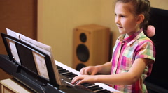 Young girl playing on a synthesizer Stock Footage