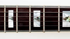 Electric guitar neck on wood panning left to right Stock Footage