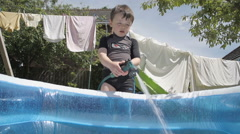 Little Boy Using A Hosepipe To Fill A Paddling Pool Stock Footage