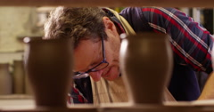 A potter shaping his work on the spinning wheel. Stock Footage