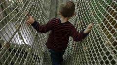 Little boy walking through rope monkey bridge Stock Footage