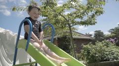Slow Motion Shot Of Boy Sliding Down Slide In Back Garden Stock Footage