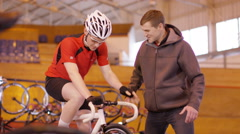 4K Young cyclist with coach, training on static bike in velodrome - stock footage