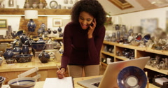An attractive African American store owner on a phone taking orders. Slow motion Stock Footage