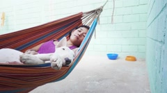 Woman and english bull terrier relaxing in hammock Stock Footage