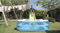 Little Boy Having Fun In An Inflatable Paddling Pool In Slow Motion Stock Footage
