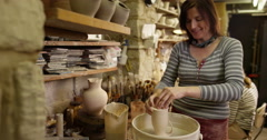 Skilled potter glazing a cup in a ceramic workshop.  Stock Footage