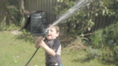 Little Boy Aiming Hosepipe At Windows In Slow Motion Stock Footage