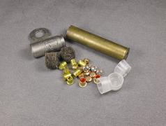 set of percussion caps and felt wad and brass shell for reloading - stock photo