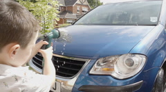 A little boy is using a hose to squirt water when cleaning a car Stock Footage