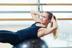 Young happy woman doing fitness exercises with fit ball at home Kuvituskuvat