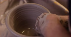 Close-up shot of a man making a ceramic pot in a workshop. Stock Footage