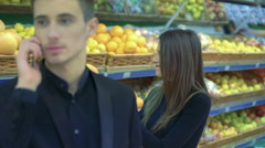 Couple in supermarket. Boy speaking on a phone, girl with fruit distracting boy Stock Footage