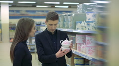 Happy young couple in furniture store choosing china cups and teapot Stock Footage