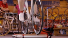 4K Cyclist training on static bike in velodrome Stock Footage