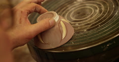 Close-up shot of a young woman at workbench painting ceramics in pottery studio. Stock Footage