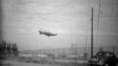 1938: Goodyear lifeguard tire blimp flying above classic car. Stock Footage