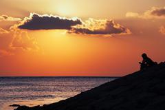 Black silhouette of thinking man sitting alone on sea beach Stock Photos