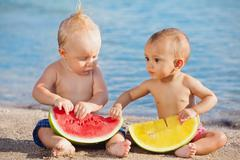 On beach asian baby girl and white boy eat fruits - stock photo