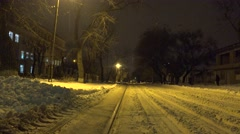 Tramway on a snowy street in the city, there is a fine snow, night Stock Footage