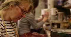 4K Workers in a pottery studio applying a decorative glaze to tea & coffee cups. Stock Footage