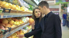 Happy couple choosing grapefruits in a supermarket Stock Footage