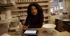 Potter woman is using a digital tablet in studio - stock footage