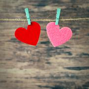 two red and  pink hearts hanging on a cord - stock photo
