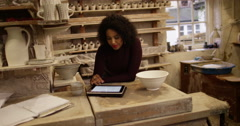 Potter woman is using a digital tablet in studio Stock Footage