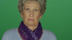 Older woman looking taken aback, on a green screen background Stock Footage
