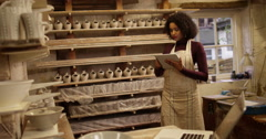 Young attractive woman checking stock at a pottery studio on her digital tablet. - stock footage