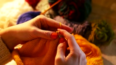 Woman Sitting And Knitting Beautiful Orange scarf, close up Stock Footage