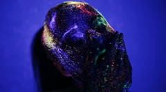 Girl in the ultraviolet glow make-up smears Stock Footage