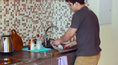 In The Kitchen Man Wash The Plates Sink in t-shirt Stock Footage